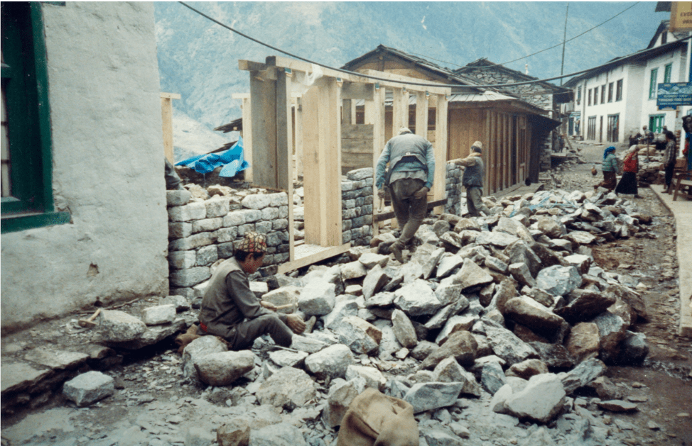 New home construction: First, hire porters to carry big rocks from the surrounding terrain. Dump them all in the middle of the unpaved street, leaving a thin trail for passers-by, yaks and very small vehicles to navigate. The masons then chisel the big rocks by hand into uni-form blocks to build the walls. No one seemed to mind the impasse on one of the few roads in this town…it's just how things are done here. Photo by Alón Sagee.